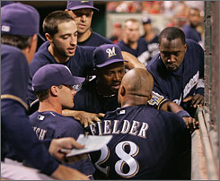 Milwaukee Brewers teammates hold back Prince Fielder after he shoved pitcher Manny Parra in the dugout during Monday's loss to the Reds.