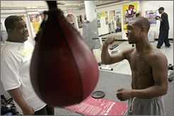 """Gary Russell Jr., right, with his father, """"Big Gary"""" Russell, works out with the speed bag at Keystone Boxing Gym in Temple Hills, Md., in preparation for the Beijing Olympics."""