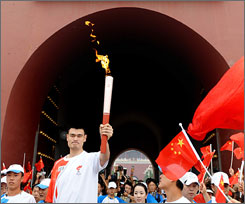 Houston Rockets and Chinese basketball star Yao Ming runs through the Tiananmen Gate Tuesday while holding the Olympic torch during the final day of the Olympic torch relay in Beijing.