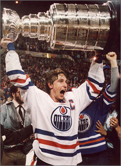 Hockey great Wayne Gretzky screams with joy as he hoists the Stanley Cup over his head following the Edmonton Oilers' win against the New York Islanders in 1984. Four years later, Gretzky would make the move to the Los Angeles Kings in one of the most shocking trades in all of sports history.