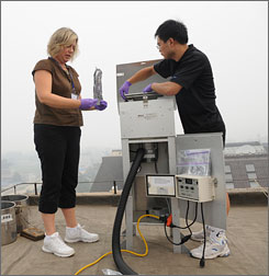 Oregon State University's Staci Simonich, left, removes and replaces filters with Peking University graduate student Wentao Wang.