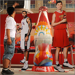 A fan looks over a Coca-Cola display featuring the United States' LeBron James and China's Yao Ming. The host Chinese have big expectations for the Games and are expected to contend with the U.S. for the most medals.