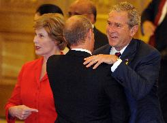 President George W. Bush gives a welcoming hug to Russian Prime Minister Vladimir Putin as Laura Bush gestures before a banquet for heads of state in the Great Hall of the People.