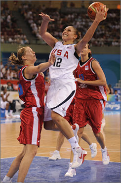 USA's Diana Taurasi gets fouled by Czech Republic's Eva Viteckova as she goes to the hoop during preliminary round action. Taurasi later scores 13 of her 17 points in the first half to lead the U.S. to the 97-57 victory.