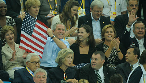 President George W. Bush waves an American flag to celebrate Michael Phelps' victory in the men's 400-meter individual medley. Joining the President were first lady Laura Bush, left, daughter Barbara, center, and his father, former president George H. W. Bush.