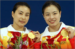 China's Guo Jingjing, left, and Wu Minxia pose with their gold medals after winning the women's 3-meter synchronized springboard diving competition.
