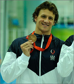 Ryan Lochte poses with his bronze medal from the men's 400-meter individual medley.