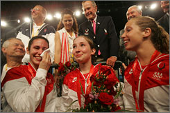 Former President George Bush meets with Sada Jacobson, left, Becca Ward and Mariel Zagunis after the Fencing Women's Individual Sabre medals ceremony. Jacobson wipes away her tears with Bush's handkerchief.