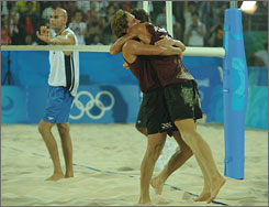 USA's Phil Dalhausser stands dejected as Aleksandrs Samoilovs and Martins Plavins celebrate their victory.