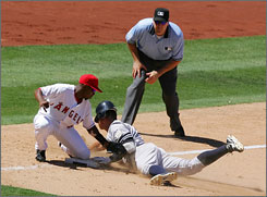 The New York Yankees Alex Rodriguez, right, is tagged out at third base in the 8th inning by the Los Angeles Angels Chone Figgins. The Angels beat the Yankees 4-3.