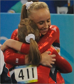 Nastia Liukin hugs USA teammate Shawn Johnson after her beam routine Sunday in Beijing.