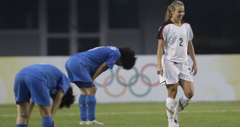 American Heather Mitts, right, walks off the pitch smiling after the U.S. beat Japan 1-0 in a first round women's match Saturday.