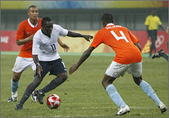 Kenneth Vermeer, left, and Kew Jaliens, right, of the Netherlands battle for the ball with Marvell Wynne of the U.S., during their men's Group B soccer match, Sunday.