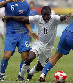 Freddy Adu, in white, powers through Japan's defense during their first round match in Tianjin, China Aug. 7.