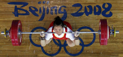 Chen Yanqing of China competes in the women's 58-kg weightlifting competition, winning the gold and setting Olympic high scores. China continues to dominate weightlifting events.