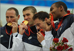The U.S. men's 4 x 100m freestyle relay team kiss their gold medals after their world record-breaking swim. Left to right: Jason Lezak, Michael Phelps, Garrett Gale-Weber and Cullen Jones.