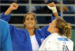 Italy's Giulia Quintavalle, left, celebrates after winning against No. 2-ranked Barbara Harel of France, during their women's 57-kg judo match.