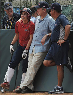 U.S. softball player Andrea Duran, left, and coach Mike Candrea, left, speak with President Bush at a training session in Beijing Saturday.