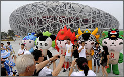 Visitors pose for photos next to Beijing's five Olympic mascots in front of the National Stadium.