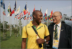 Sprinter Asafa Powell, left, of Jamaica chats with Mike Fennell, chief of the Jamaica Olympic Association, at a flag-raising ceremony ahead in Beijing Aug. 5.