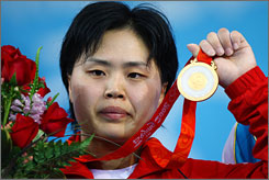 Hyon Suk Pak of The People's Republic of Korea holds up her country's first weightlifting gold medal, which she clinched in the last lift of the 63-kg (138.8-pound) competition.