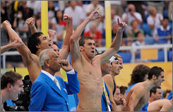 Michael Phelps and his teammates cheer on Peter Vanderkaay as he finishes the final leg of the 4x200m freestyle relay. The team easily won the event with a world record and Phelps picked up his fifth gold medal of this Olympics.
