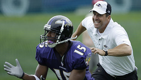 New Ravens coach John Harbaugh got in on the action at training camp, here defending receiver Patrick Carter during a drill on July 23.