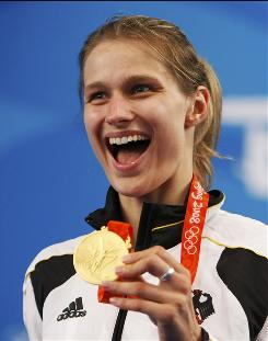 Britta Heidemann of Germany shows off her gold medal after the women's individual epee fencing competition.