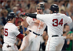 The Boston Red Sox's Kevin Youkilis, center, celebrates his three-run home run that drove in Dustin Pedroia, left, and David Ortiz, right, in the eighth inning against the Texas Rangers. Youkilis and Ortiz both hit two homers in the game to slug the Red Sox past the Rangers 19-17.