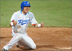 Lee Jong-wook is ecstatic after crossing home plate to lift South Korea over the USA 8-7.