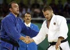 Georgia's Irakli Tsirekidze, left, shakes hands with Russia's Ivan Pershin. Their countries are in conflict, but they &quot;are friends&quot; says Tsirekidze.