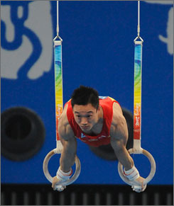 Yang Wei, performing his routine on the rings, added an Olympic gold medal to his two world championships.