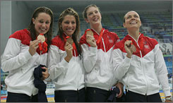 First time Olympian Caroline Burckle, second left, shows off her bronze medal along with 4x200 freestyle relay teammates Katie Hoff, left, Allison Schmitt and Natalie Coughlin.