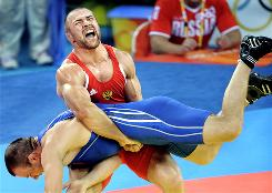 Russia's Aslanbek Khushtov screams as he flips opponent Lithuanian wrestler Mindaugas Ezerskis in a semifinal match.
