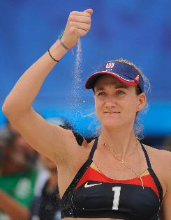 USA's Kerri Walsh tests the wind after the prematch coin toss. Her shoulder has survived some tests as well. She uses black kinesio tape which she says helps with circulation.