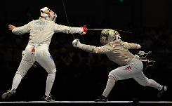 USA's Mariel Zagunis, right, battles France's Leonore Perrus in team sabre competition. USA prevailed 45-38 to win the bronze medal.