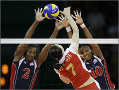Danielle Scott-Arruda, left, and Kimberly Glass of the USA block a shot by China's Zhou Suhong. The Americans defeated the home team with Chinese President Hu Jintau in attendance.