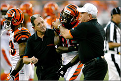 Trainers help Bengals receiver Chad Johnson off the field after he hurt his shoulder on Sunday night.