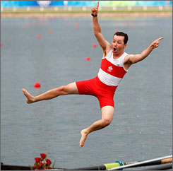 Canada's coxswain Brian price was tossed into the water after his team took gold in the eight man rowing competition Sunday.