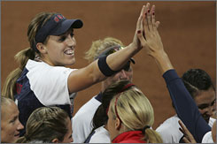 Monica Abbott is congratulated by the U.S. softball team after pitching five perfect innings in the team's 8-0 win over the Netherlands on Sunday night in Beijing.