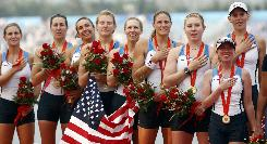 The U.S. team that won the gold medal in the women's rowing eight competition is all smiles on the victory stand.