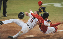 Nate Schierholtz collides with Chinese catcher Yang Yang while scoring during the USA's 9-1 victory on Monday.