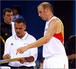 Chris Kaman, right, confers with German coach Dirk Bauermann during a Group B game against Spain. You can bet they're not conferring in German.