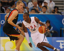 Team USA guard Kobe Bryant, right, drives around Germany's Jan-Hendrik Jagla during their preliminary game at Olympic Basketball Gymnasium on Monday, which the Americans won 106-57.
