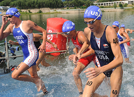 Americans Laura Bennett, right, and Sarah Haskins leave the swim phase of the triathlon on Monday morning in Beijing.