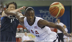 Sylvia Fowles, who finished with 26 points, chases a loose ball in front of South Korea's Jung Sunmin. The unbeaten Americans won by 44 points.