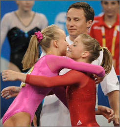 Nastia Liukin, left, hugs Shawn Johnson during the all-around finals as Liukin's father Valeri, who won four medals in artistic gymnastics, including two golds, for the Soviets 20 years ago, looks on.