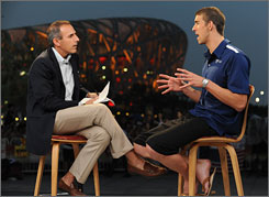 Today show host Matt Lauer, left, and Michael Phelps chat animatedly on the set, on the Olympic Green with Beijing's National Stadium lit up behind them.