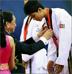Rohullah Nikpai receives Afghanistan's first-ever Olympic medal, a bronze in taekwondo.