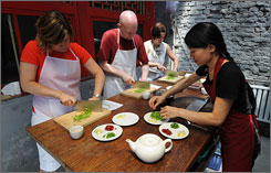Chinese chef Chunyi Zhou, right, conducts a cooking class for three U.S. tourists at her traditional hutong courtyard style house in Beijing.